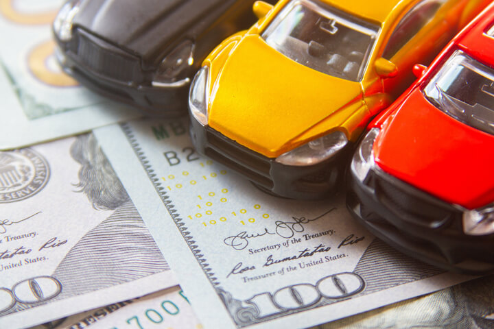 Photo of black, yellow, and red toy cars on scattered 100 dollar bills