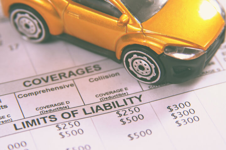 Car insurance policy showing liability limits with toy car