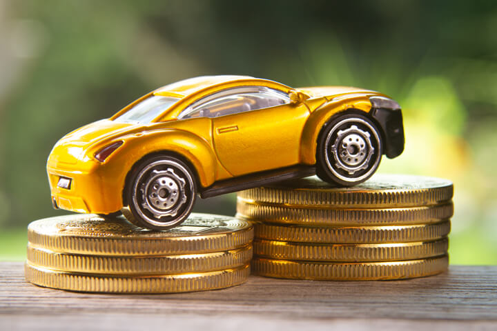 Angled view photo of yellow toy car climbing two stacks of gold coins