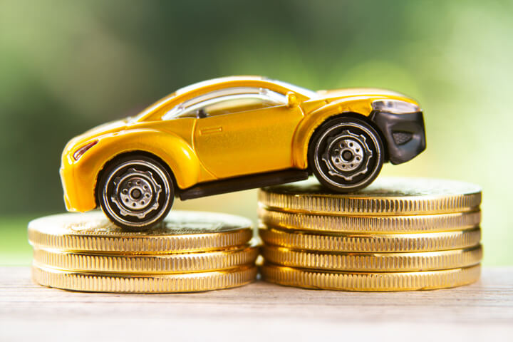 Yellow toy car climbing two stacks of gold coins