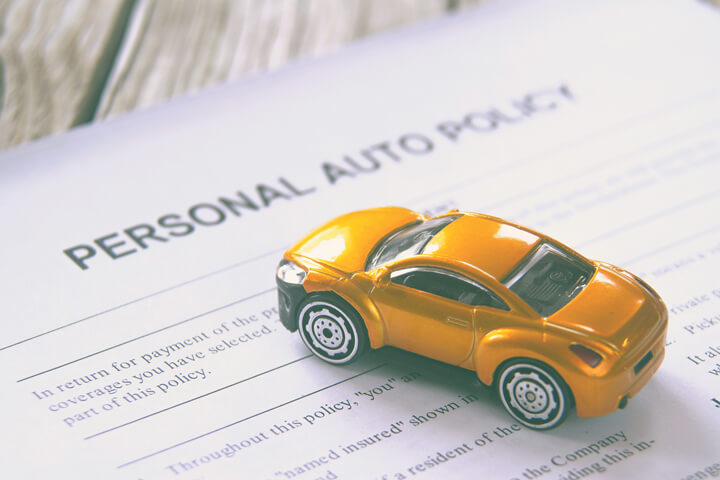 Personal auto insurance policy with small toy car