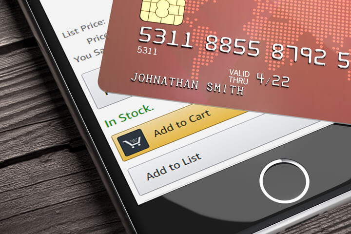 Credit card lying on top of iPhone with Amazon app visible on screen with focus on Add to Cart button
