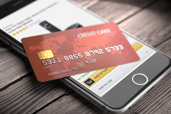 Credit card lying on iPhone with Amazon app visible on screen online purchase concept