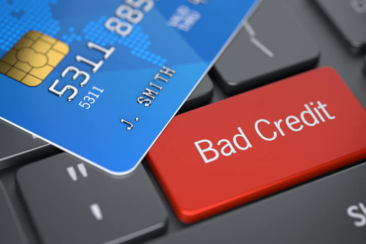 Bright red Bad Credit key on dark laptop keyboard with blue credit card lying on top