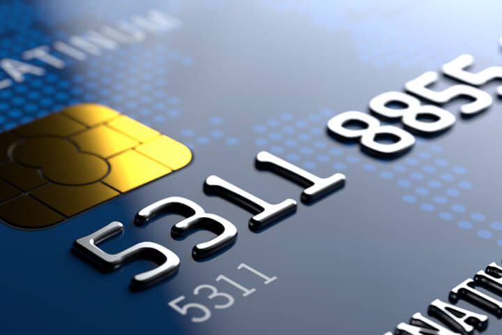 Close up view of credit card from corner angle showing partial number and EMV chip