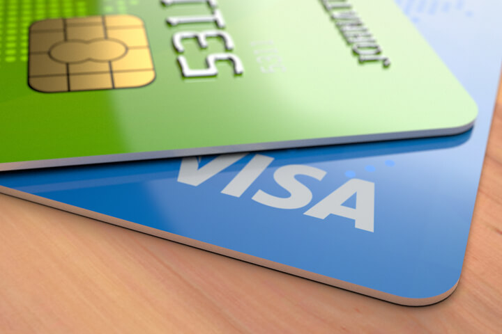 Blue and green credit cards with EMV chip on wood desk
