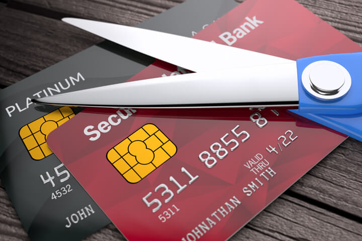 Two credit cards on weathered wood planks with scissors