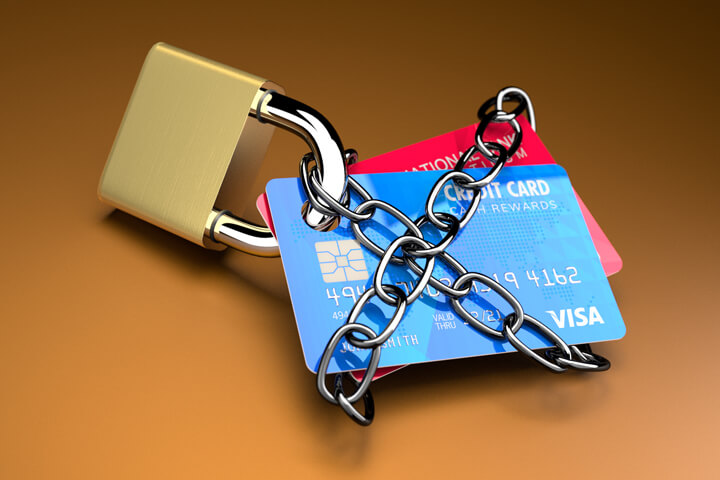 Credit cards padlocked and chained on orange background