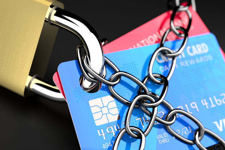 Close up photo of chains wrapping credit cards with padlock