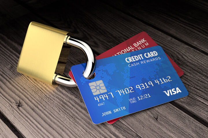 Photo of two credit cards padlocked on old wood surface