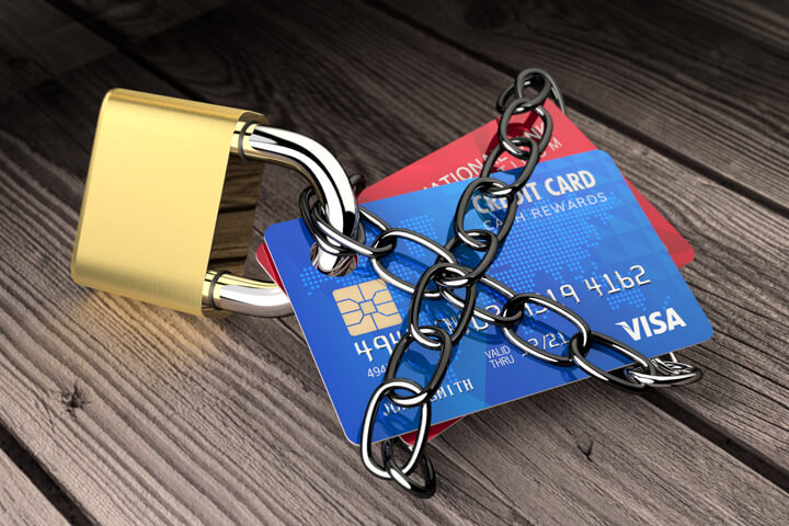 Two credit cards chained to padlock on wood planks