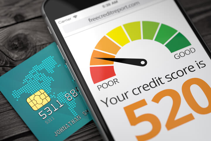 Cell phone screen showing poor credit rating on top of credit card with EMV chip