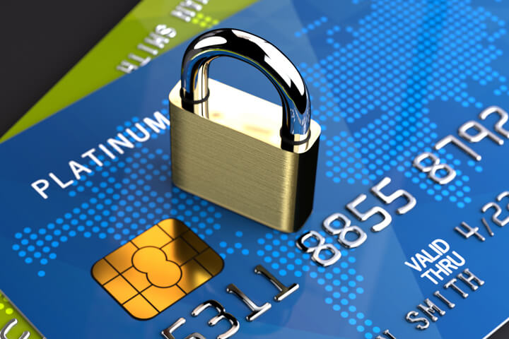 Two angled credit cards on dark background with small padlock on top