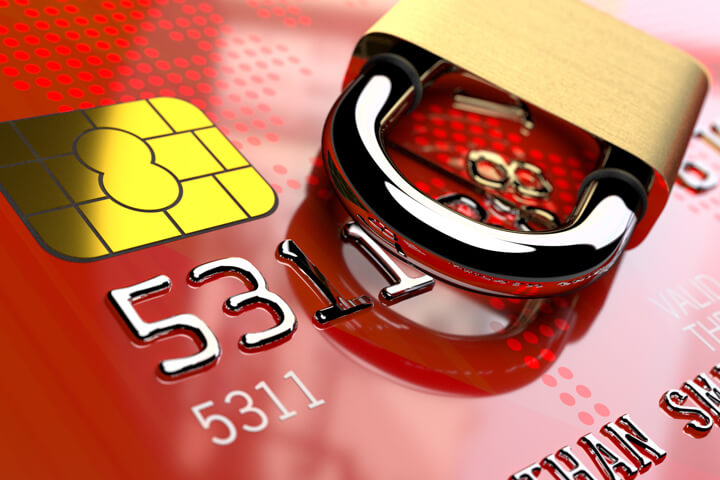 Angled view of red credit card EMV chip with padlock lying on side