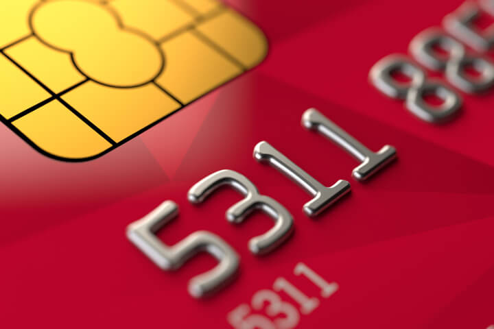 Close up view of red credit card EMV chip and credit card number
