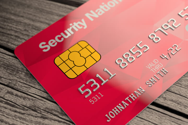 Red credit card lying on wood plank background