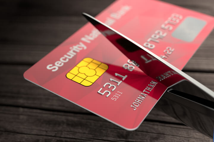 Scissors cutting through red credit card with wood plank background