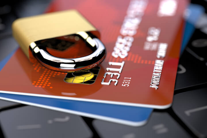Two credit cards on keyboard with small padlock lying on top