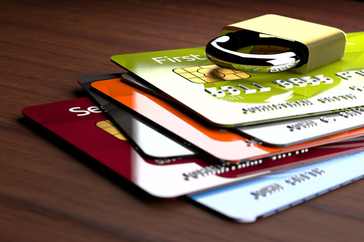 Stack of shiny credit cards with small padlock on top