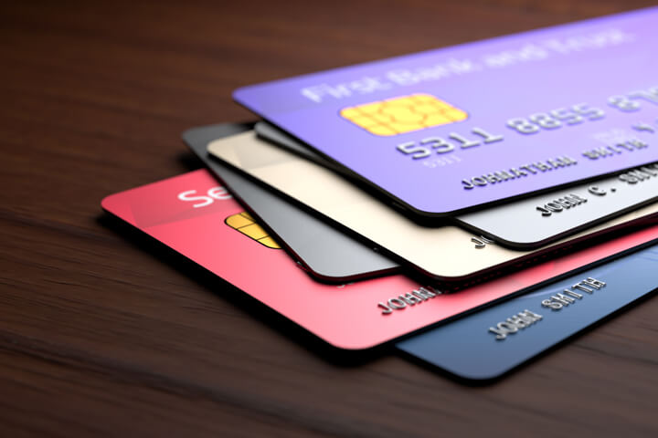 Stack of multicolored credit cards on wood desk or table