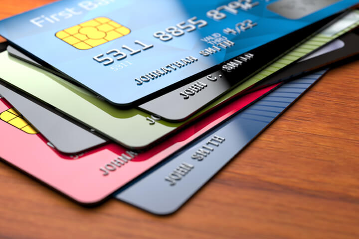Stack of shiny credit cards on rich wood surface