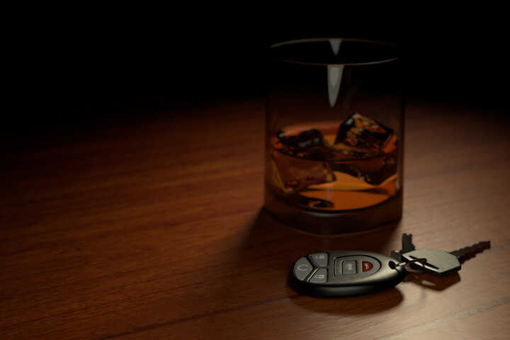 Drunk driving concept showing alcoholic drink on bar with car keys in foreground