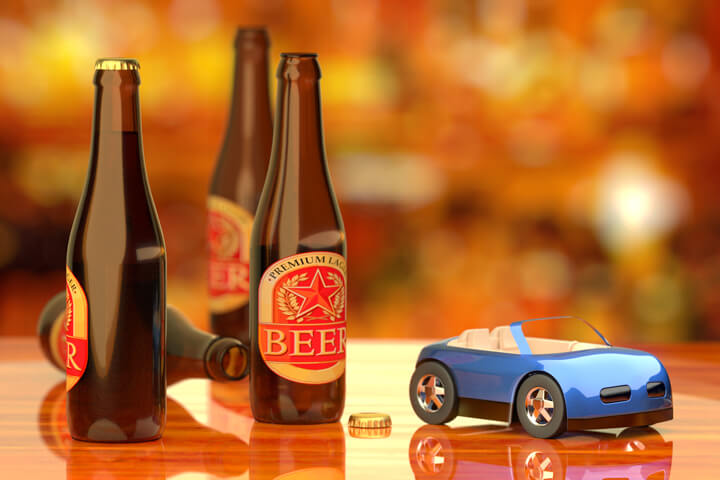 Beer bottles on bar next to blue toy car concept for drinking and driving or driving while intoxicated