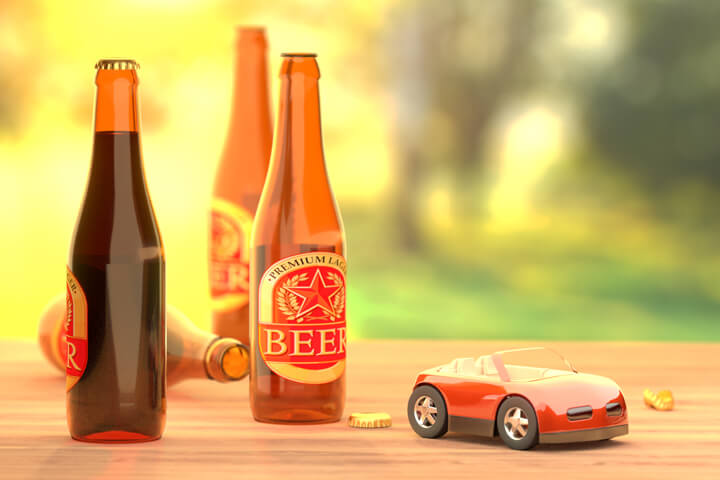 Beer bottles on table outside with red toy car concept for driving under the influence or drunk driving