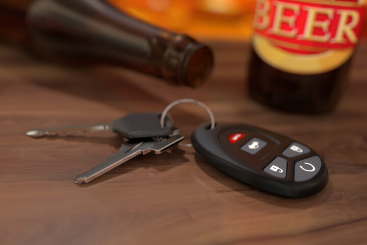 Car keys on wood bar with beer bottles in background