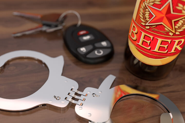 Car keys with hand cuffs and a beer bottle sitting on bar free DUI image