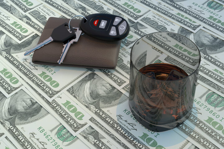 Glass of whiskey, wallet, and car keys on top of money concept for the cost of driving under the influence
