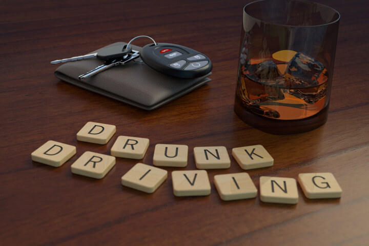 Drunk driving concept showing a glass of whiskey and car keys behind wooden letters spelling drunk driving