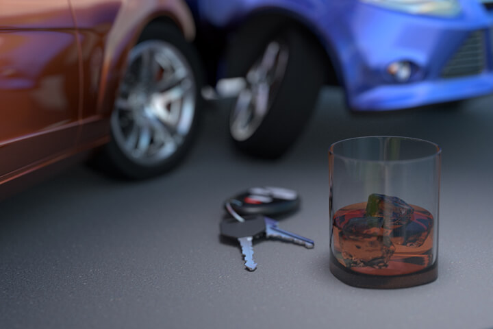 Side impact collision resulting from drunk driving concept with whiskey glass and car keys in foreground