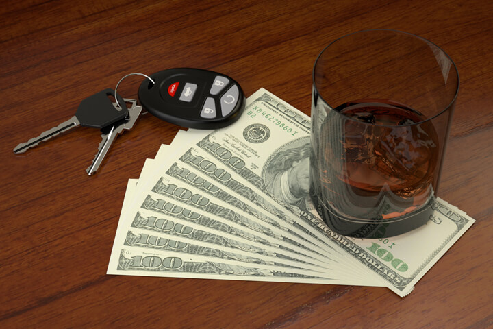 Glass of whiskey and car keys on top of fanned one hundred dollar bills representing the cost of a DUI conviction