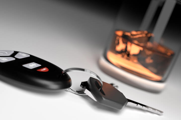 Drunk driving concept showing whiskey glass and car keys on white studio background