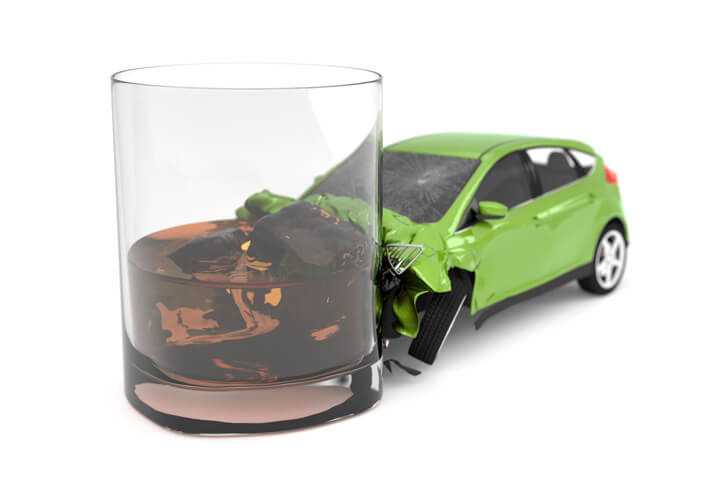 Drunk driving concept of small green car collision with alcoholic drink isolated on white background