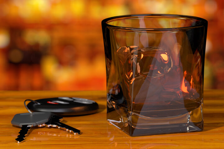 Whiskey glass and car keys on bar with liquor bottle background DUI concept