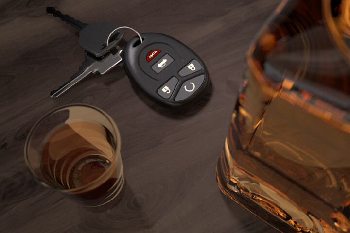 Whiskey bottle and shot glasses on wood bar with car keys DUI concept image