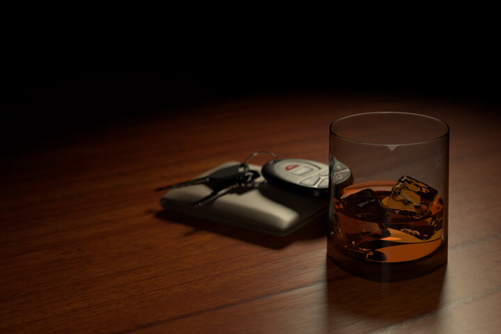 Drunk driving concept showing a whiskey glass on bar with wallet and car keys another view