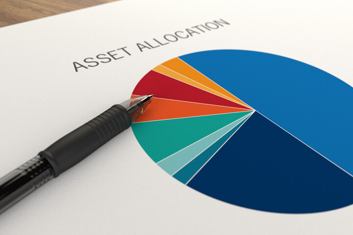 Paper with asset allocation pie chart overlaid with ballpoint pen on table
