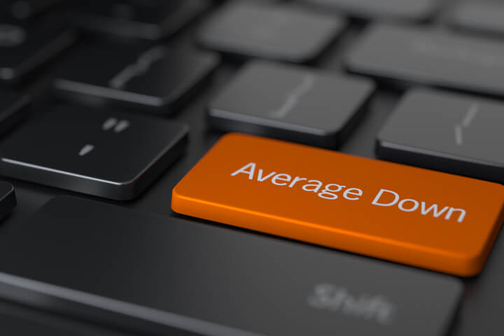 Dark laptop keyboard with large orange Average Down key representing the average down investment strategy