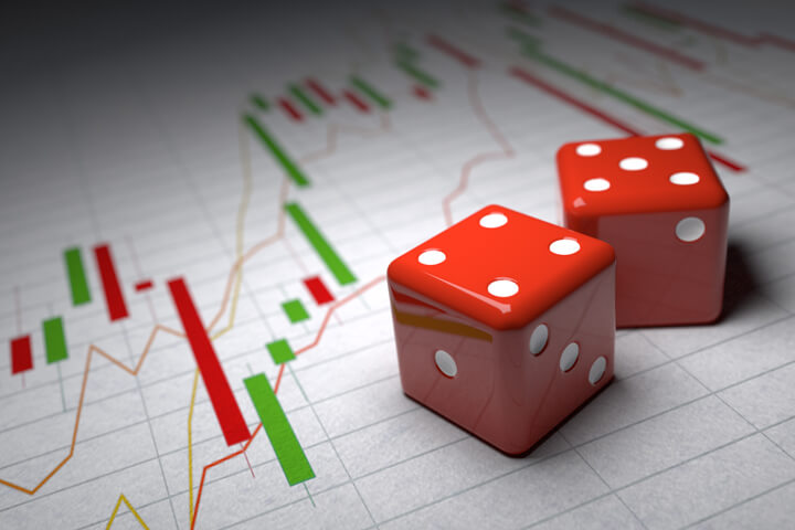 Concept of speculation risk showing red dice on candlestick and line charts for stock and market prices