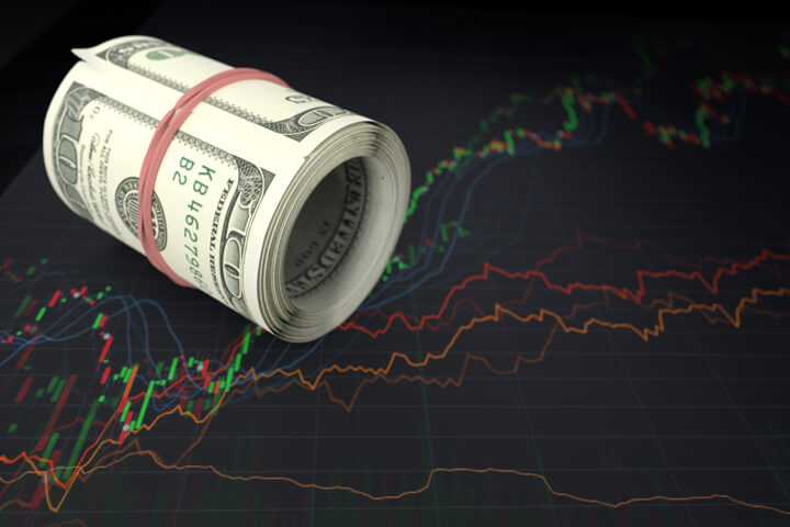 Large roll of U.S. bills laying on top of line charts showing massive stock price fluctuation