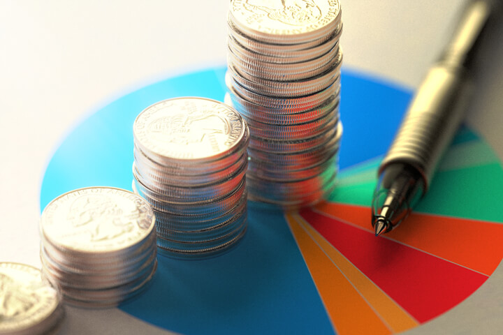 Paper with asset allocation pie chart, stacks of coins, and ballpoint pen