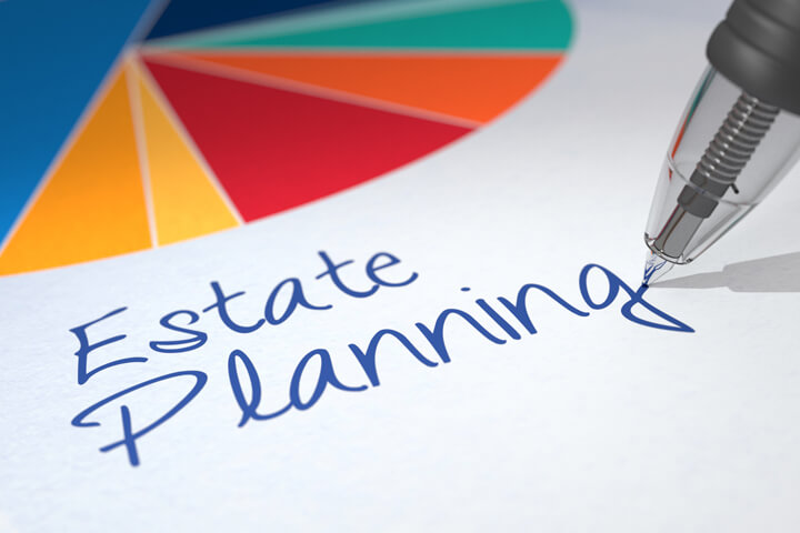 Colorful pie chart on paper with ballpoint pen writing Estate Planning beneath