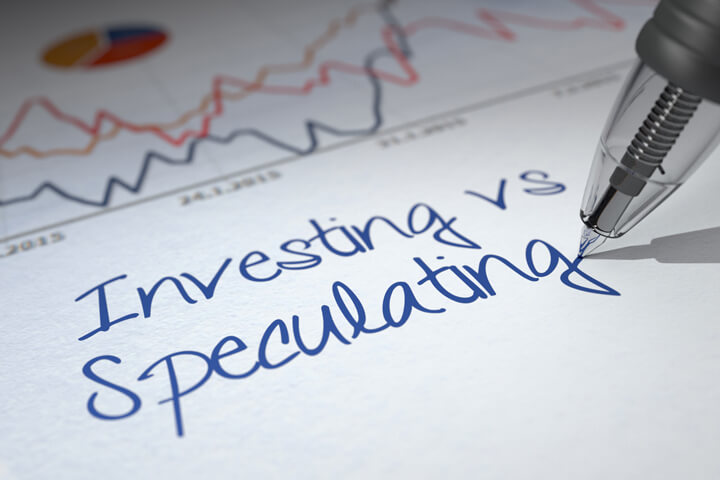 Paper with investment charts and words Investing vs Speculating written with ballpoint pen