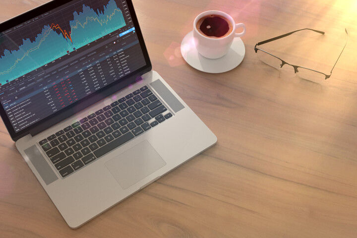 Laptop with stock price screen on table with glasses and coffee cup with lighting flare effect