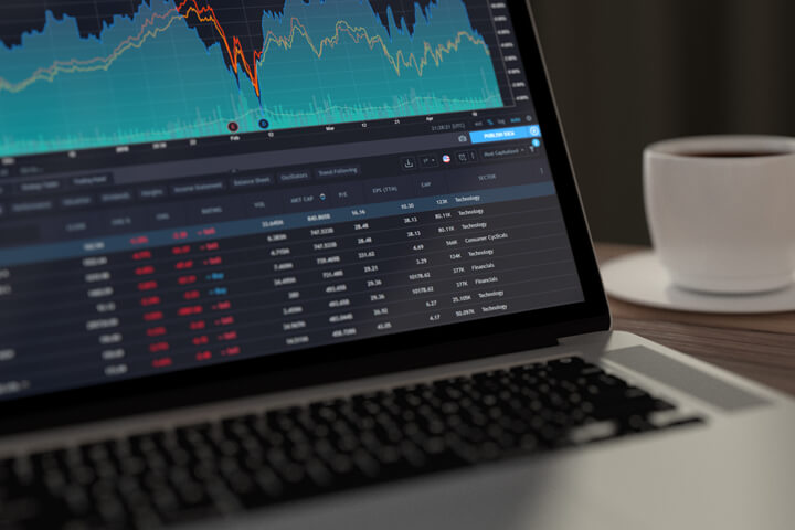 Laptop showing stock prices and area chart with coffee cup in background