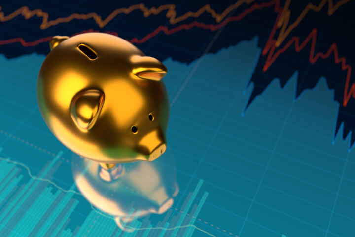 Shiny gold metallic piggy bank on stock price area chart with glossy surface reflection