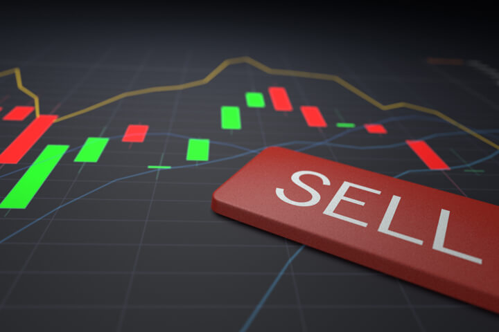 Sell keyboard key on stock price candlestick chart representing stock sale
